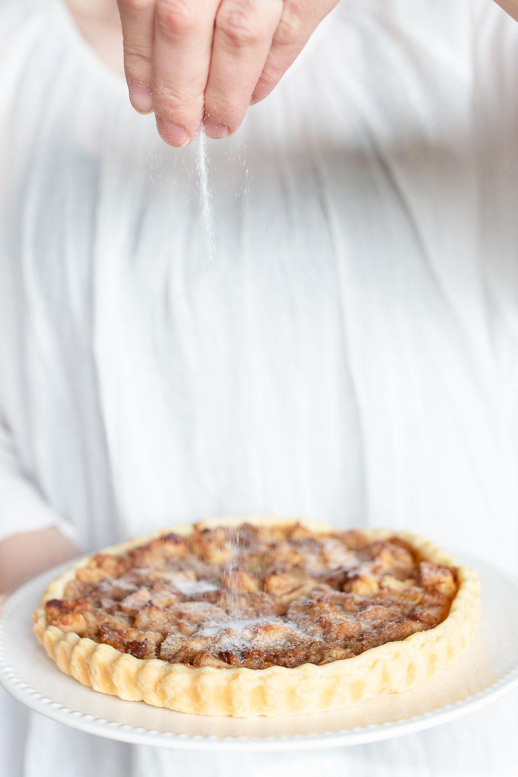 sprinkling sugar on the apple pie