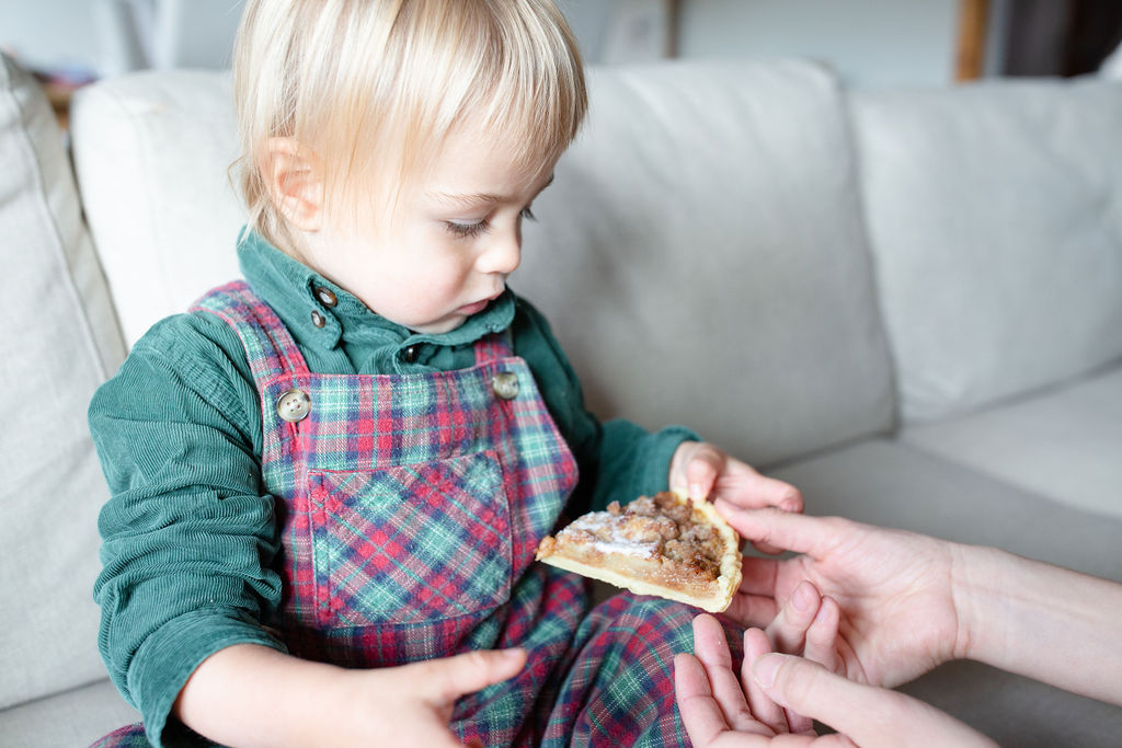 hands giving a pie slice to a toddler