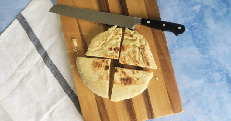 round semolina bread sliced in quarters on a wooden chopping board with a knife