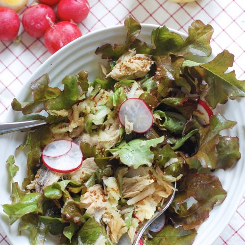 A bowl of mackerel salad with radishes and Lemons in background