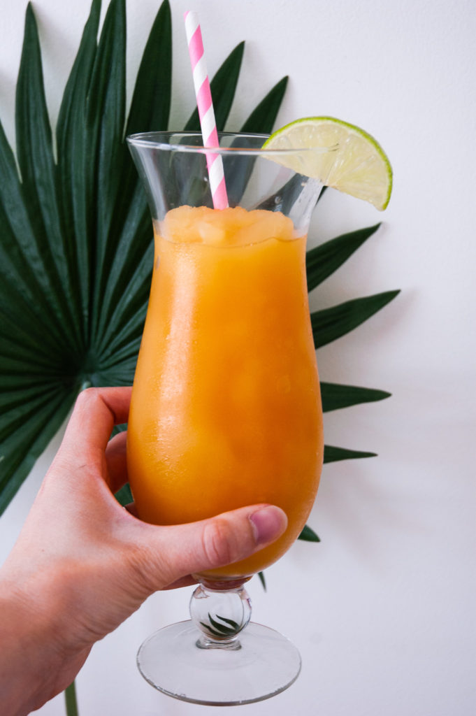 A hand holds the Pineapple and Orange Rum Slush in front of a palm leaf