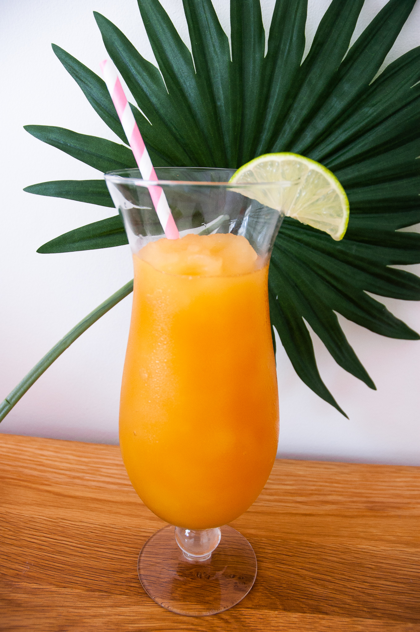 Pineapple and Orange Rum Slush in a tall glass in front of a palm leaf