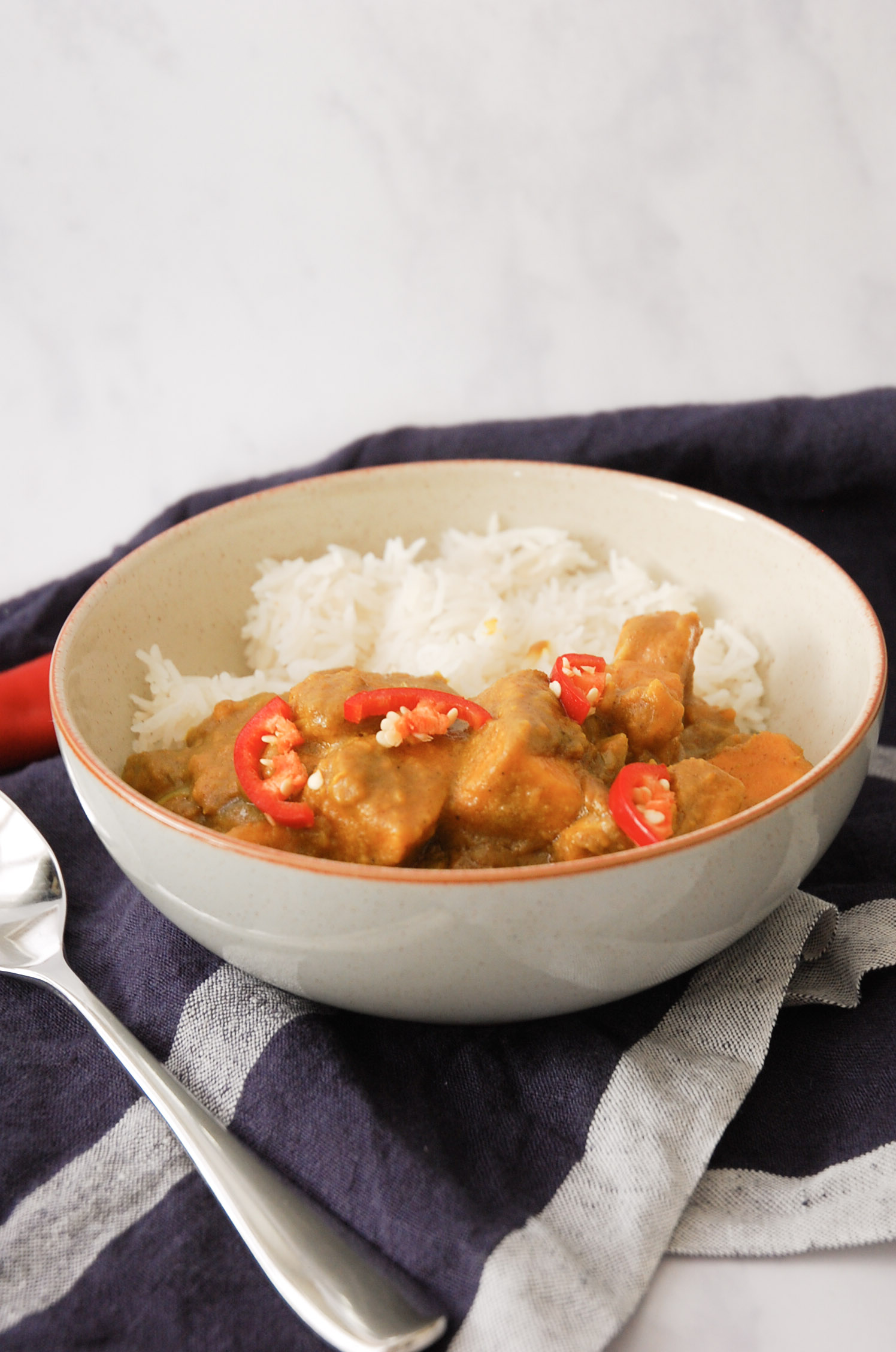 sweet potato curry in a grey bowl with a spoon on the left