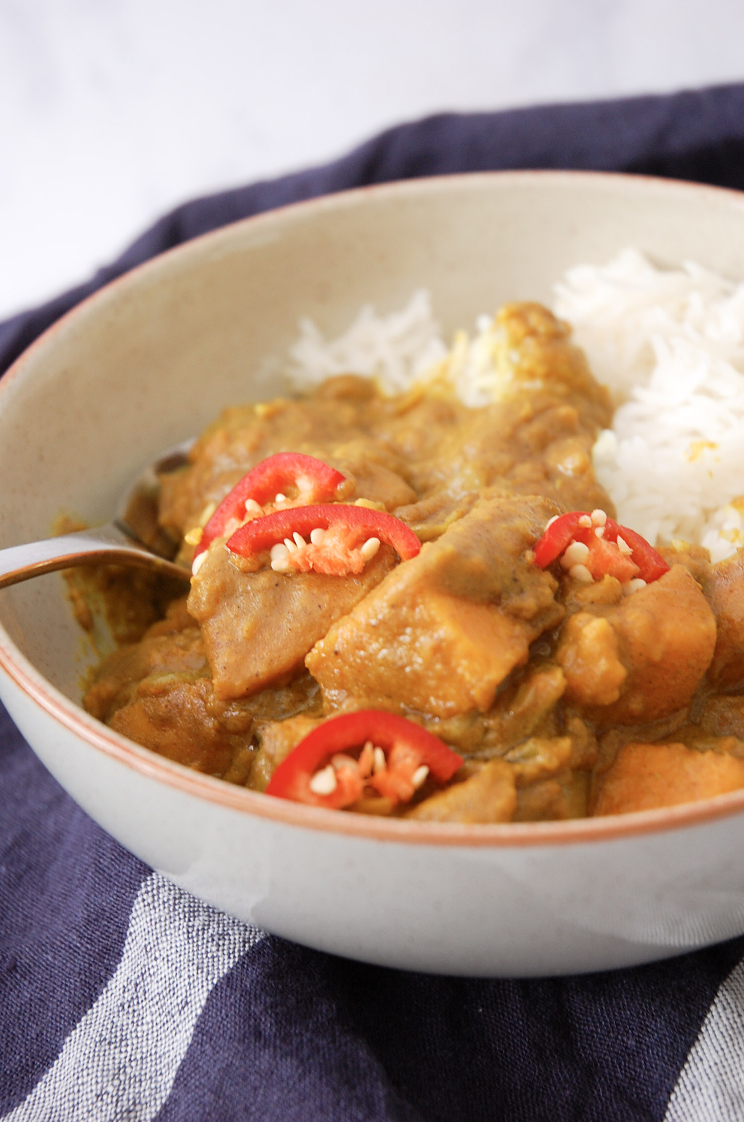 sweet potato curry in a grey bowl on top of a navy linen