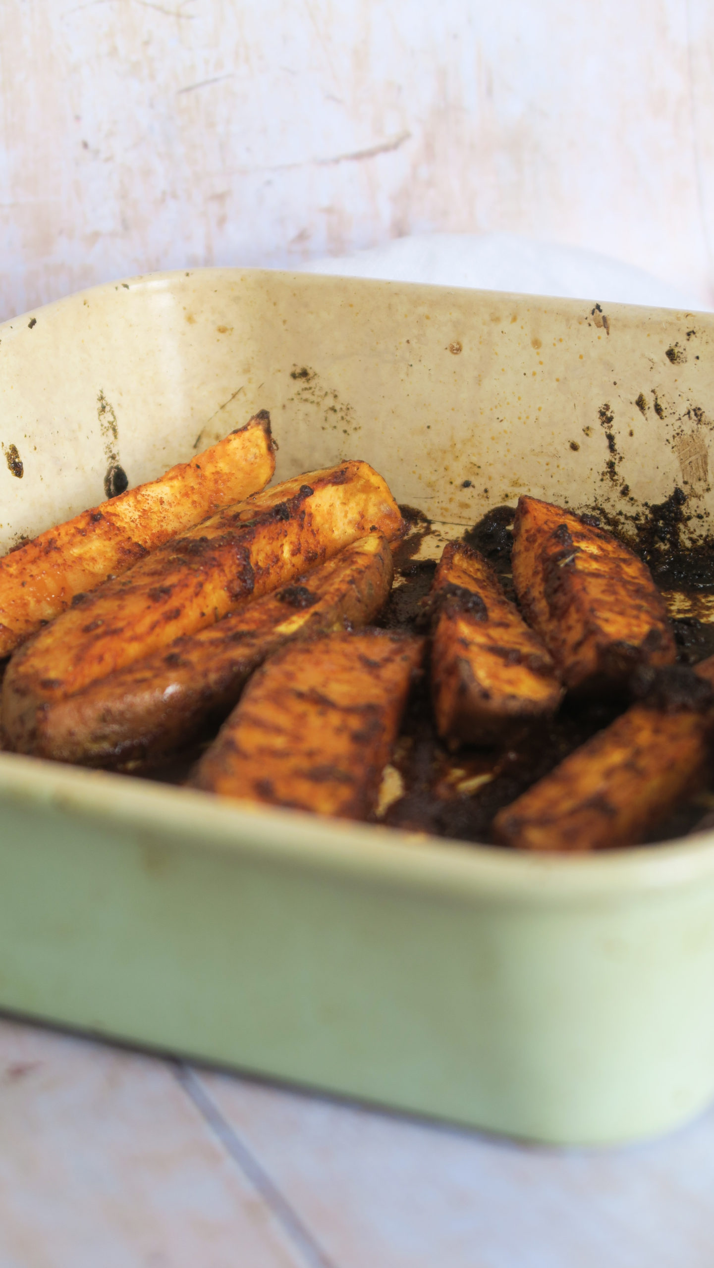 Peri peri sweet potato wedges in a green baking tray