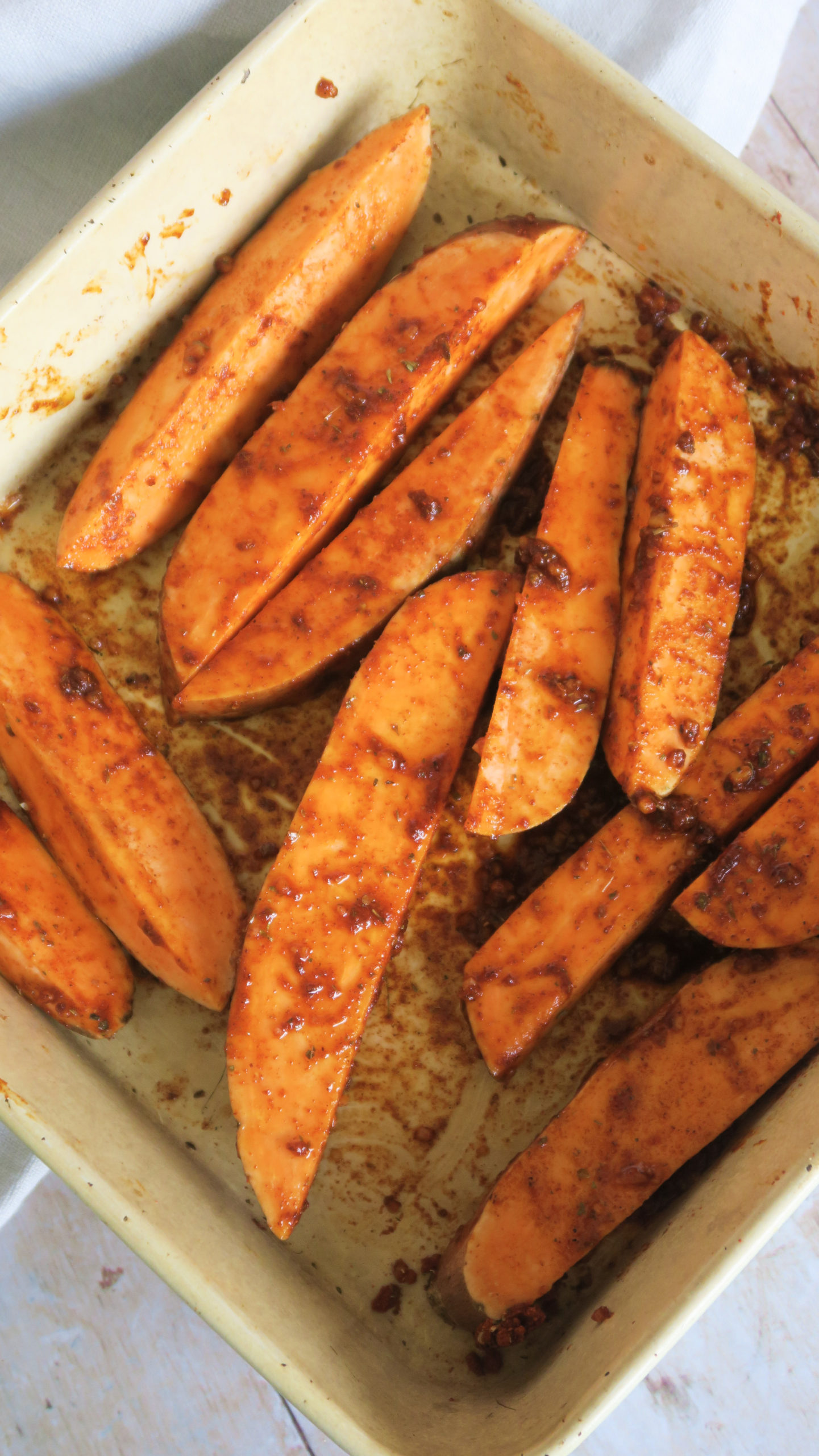 Sweet potato wedges pre-cook in a baking tray