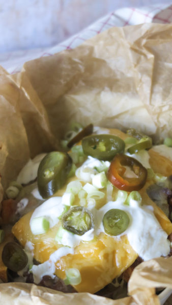 cheesy chili topped with sour cream and jalapeños on a some brown greaseproof paper