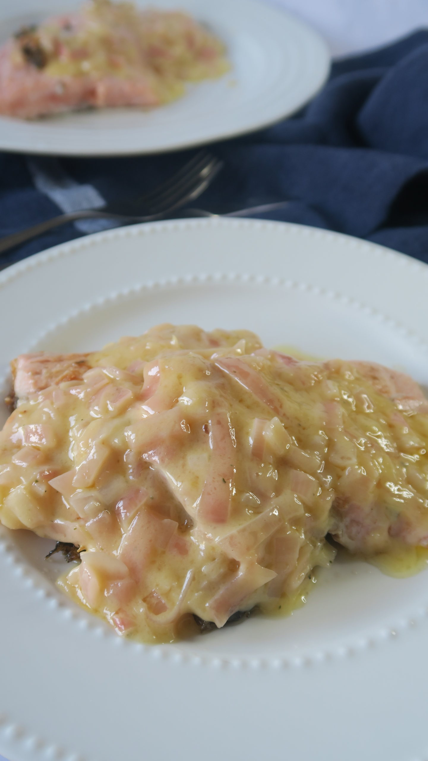 A white plate on top of navy linen with two pieces of salmon covered in creamy butter sauce