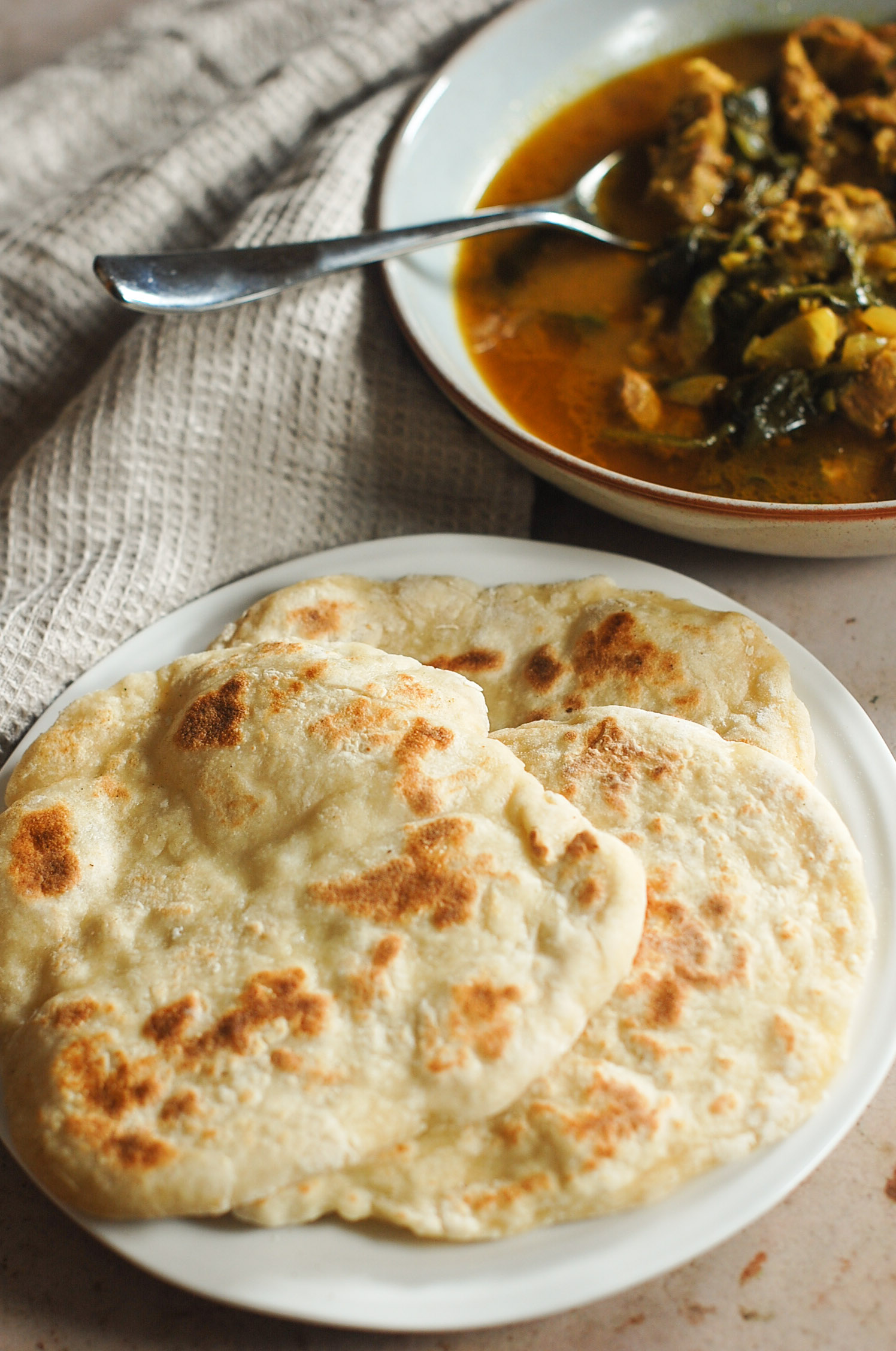 Naan bread with curry in the background