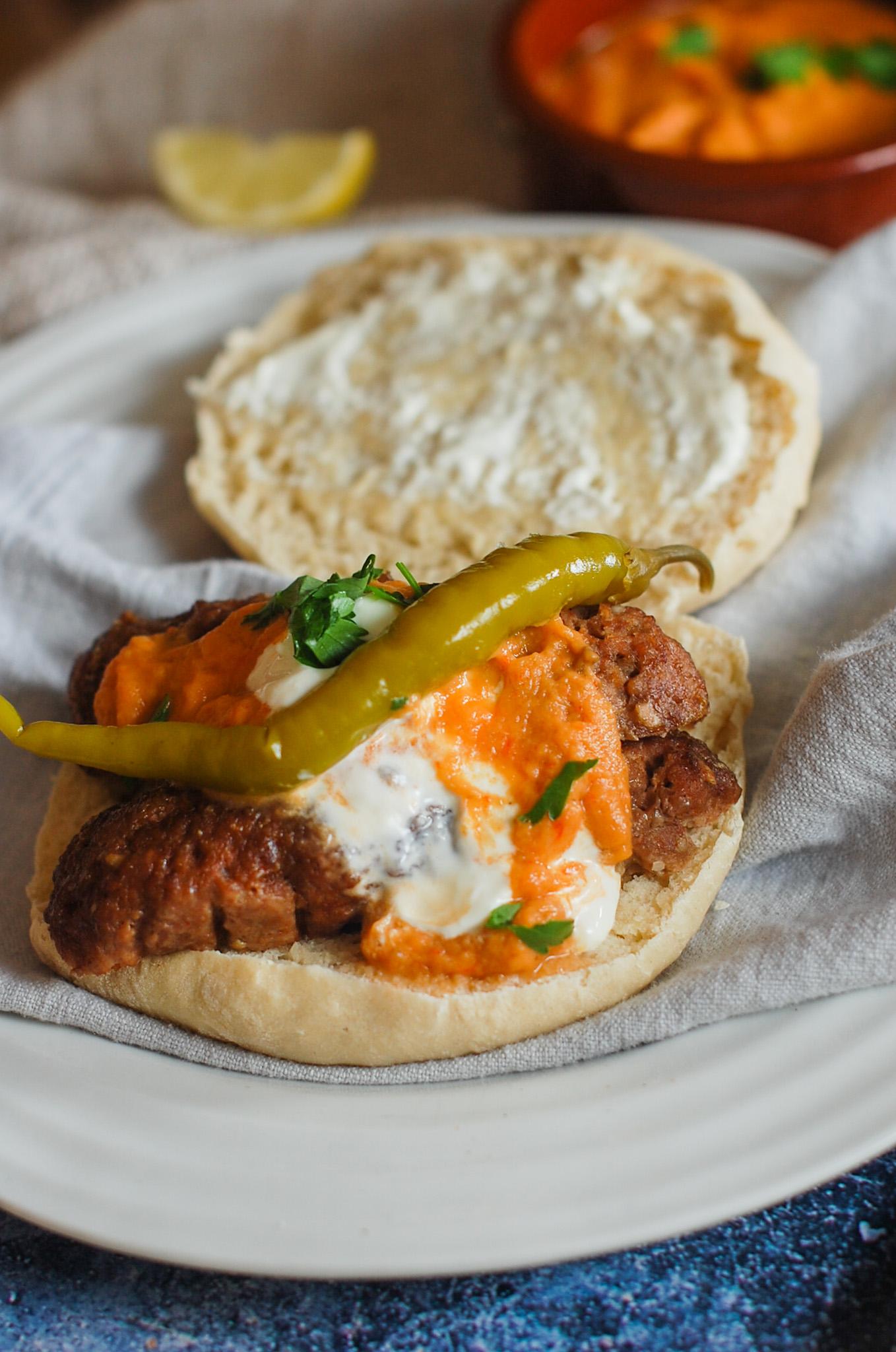 cevapi in lepinja bread with ajvar sauce topping