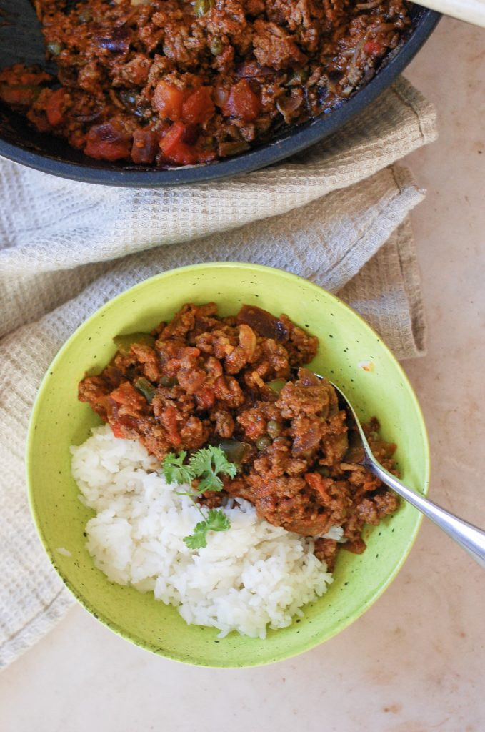 a green bowl full of beef picadillo and rice.