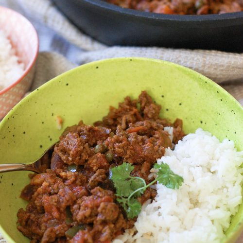 a green bowl with picadillo and rice