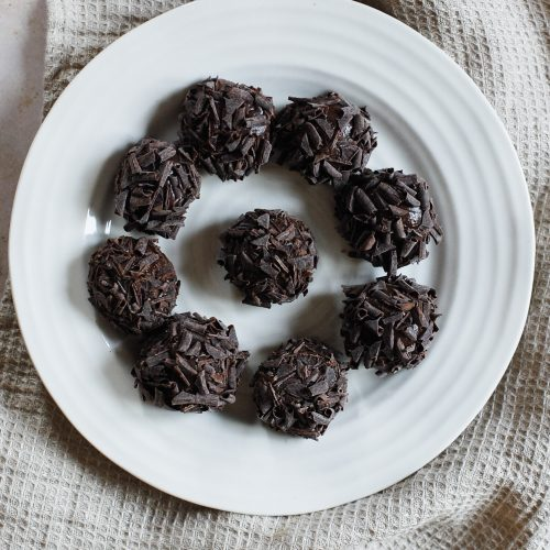 a white plate with chocolate truffles on top